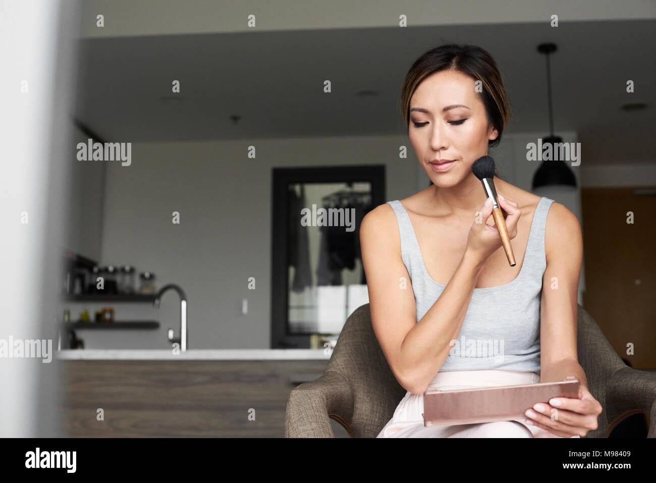 La donna di casa utilizzando lo specchio a mano applicando il trucco Immagini Stock