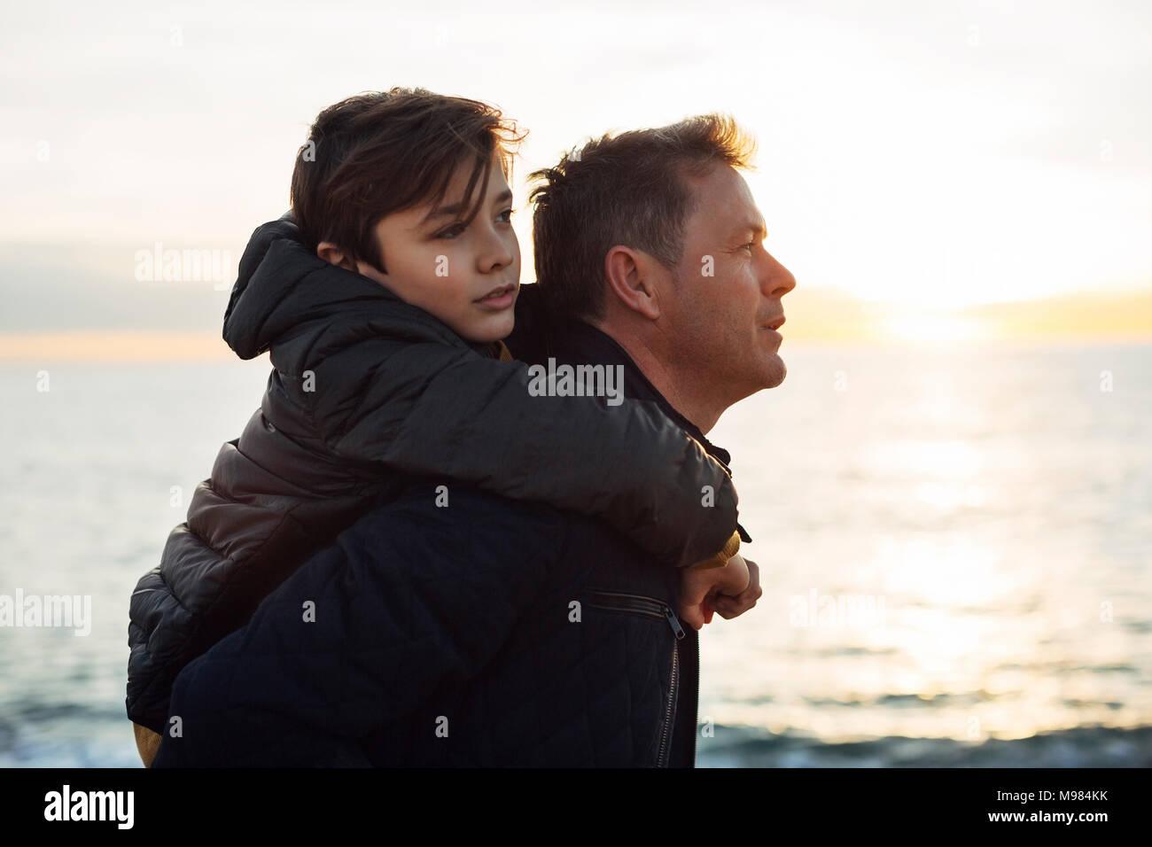 Padre figlio portante sovrapponibile in riva al mare Immagini Stock