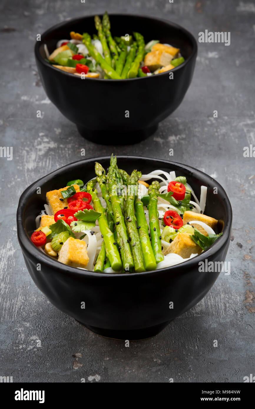 La vaschetta del vegan Pad Thai con mini asparagi verdi e tofu, peperoncino, cipolline, arachidi e coriandolo Immagini Stock