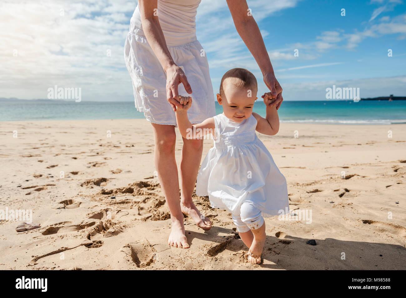 Madre aiutare piccola figlia di camminare sulla spiaggia Foto Stock