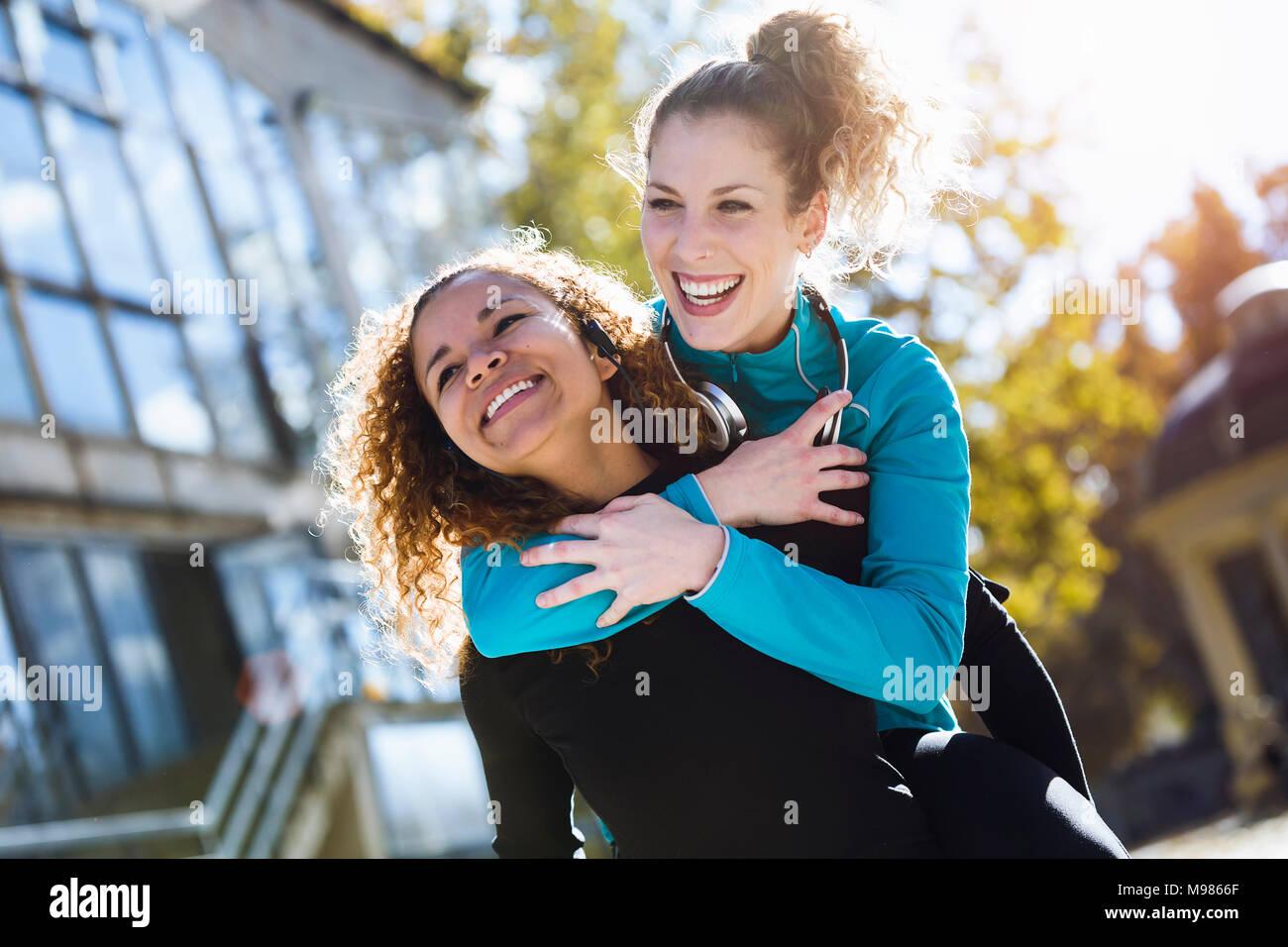 Felice giovane donna che trasportano amico piggyback Immagini Stock