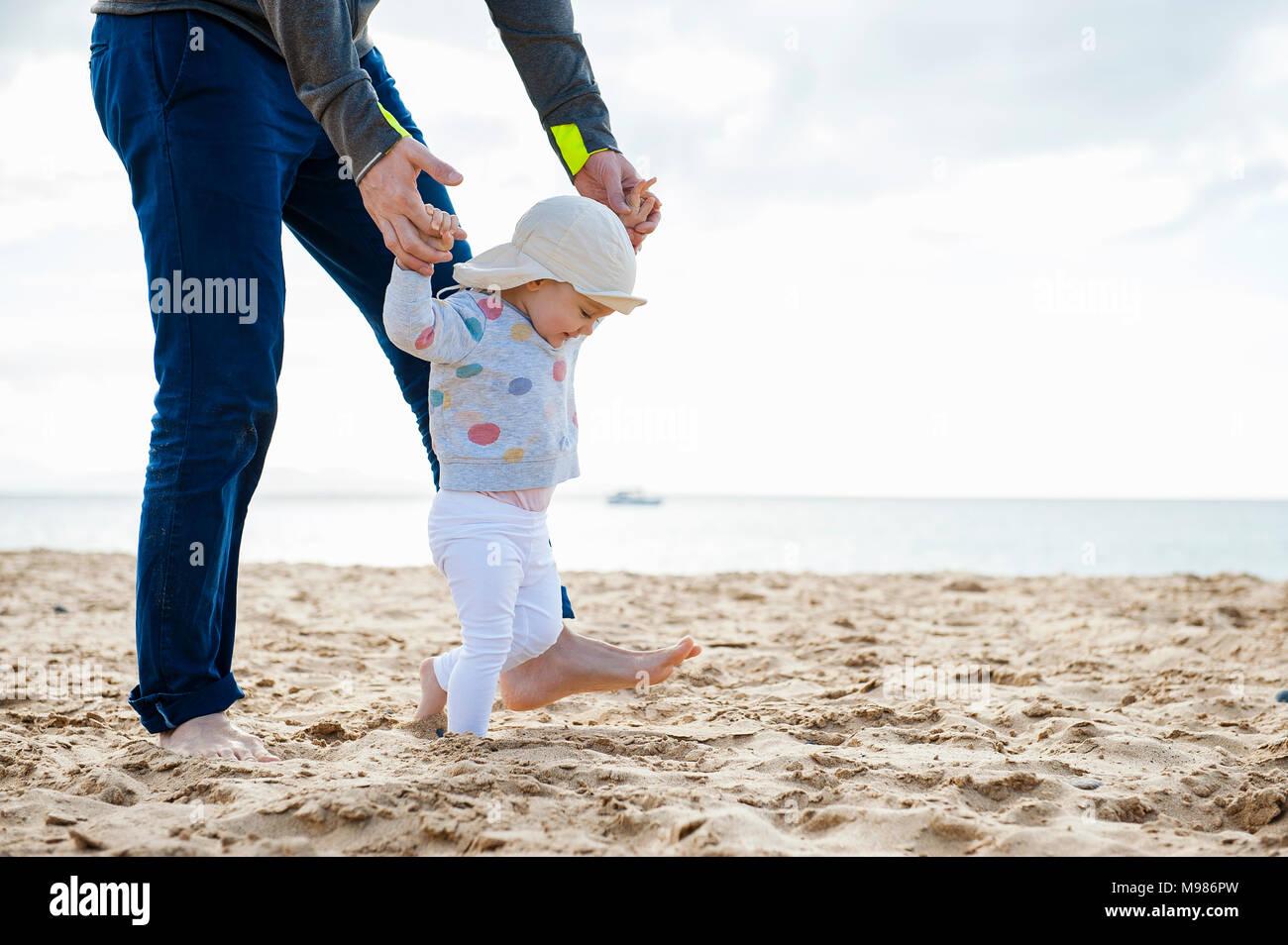 Spagna Lanzarote, baby ragazza camminare sulla spiaggia con l aiuto di suo padre Immagini Stock