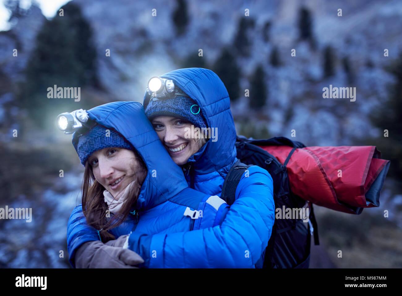 Felice di due giovani donne che indossano i proiettori abbracciando in montagna Immagini Stock