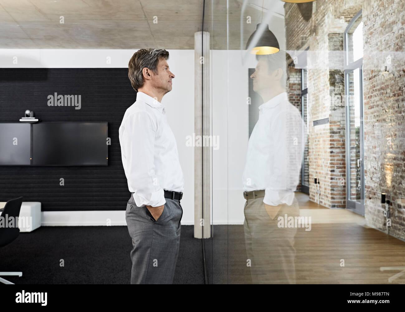 Imprenditore maturo che riflette nella lastra di vetro di una moderna sala conferenze Immagini Stock