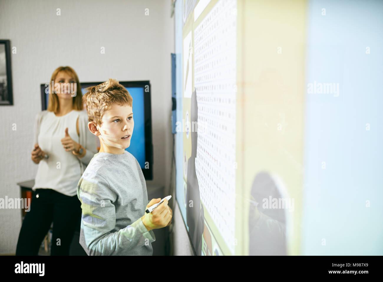 Studente in classe alla lavagna interattiva con insegnante in background Immagini Stock