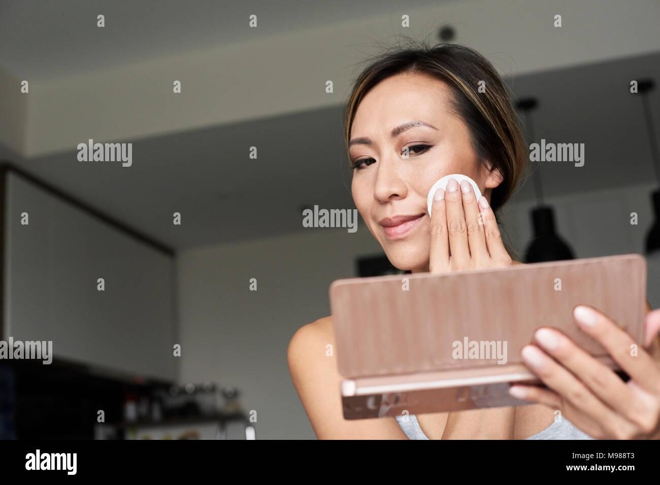 La donna di casa utilizzando lo specchio a mano la rimozione di trucco con tampone di cotone Immagini Stock