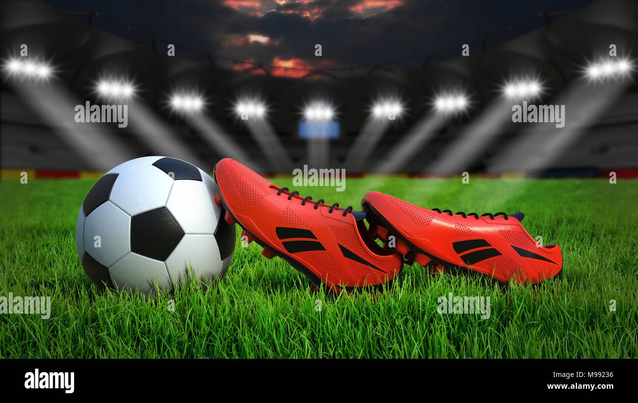Pallone da calcio e scarpe su erba in stadio con illuminazione