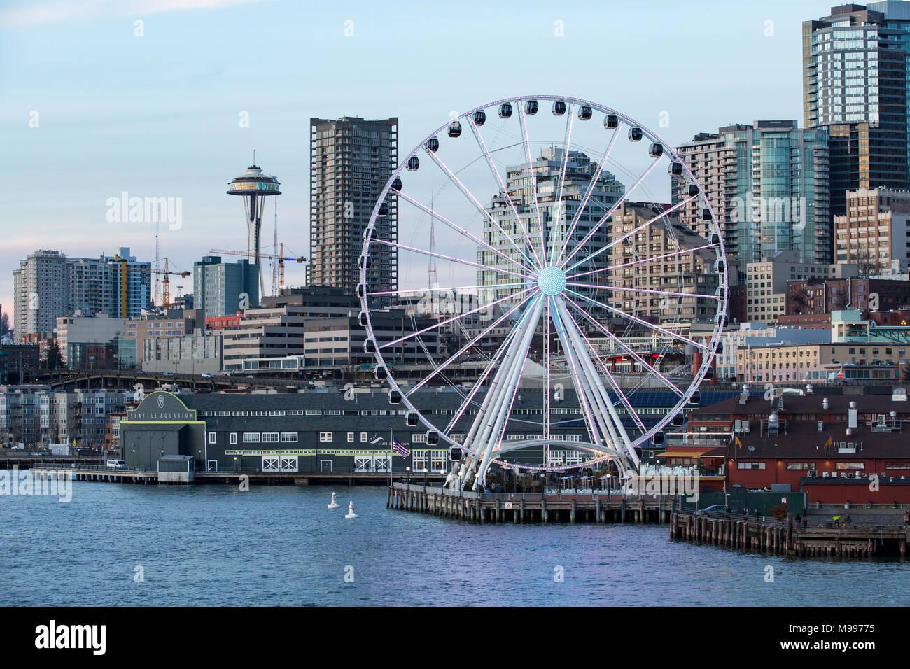 Lo skyline di Seattle Waterfront al tramonto con Seattle lo Space Needle e il Seattle grande ruota, ruota panoramica Ferris, Seattle Washington. Immagini Stock