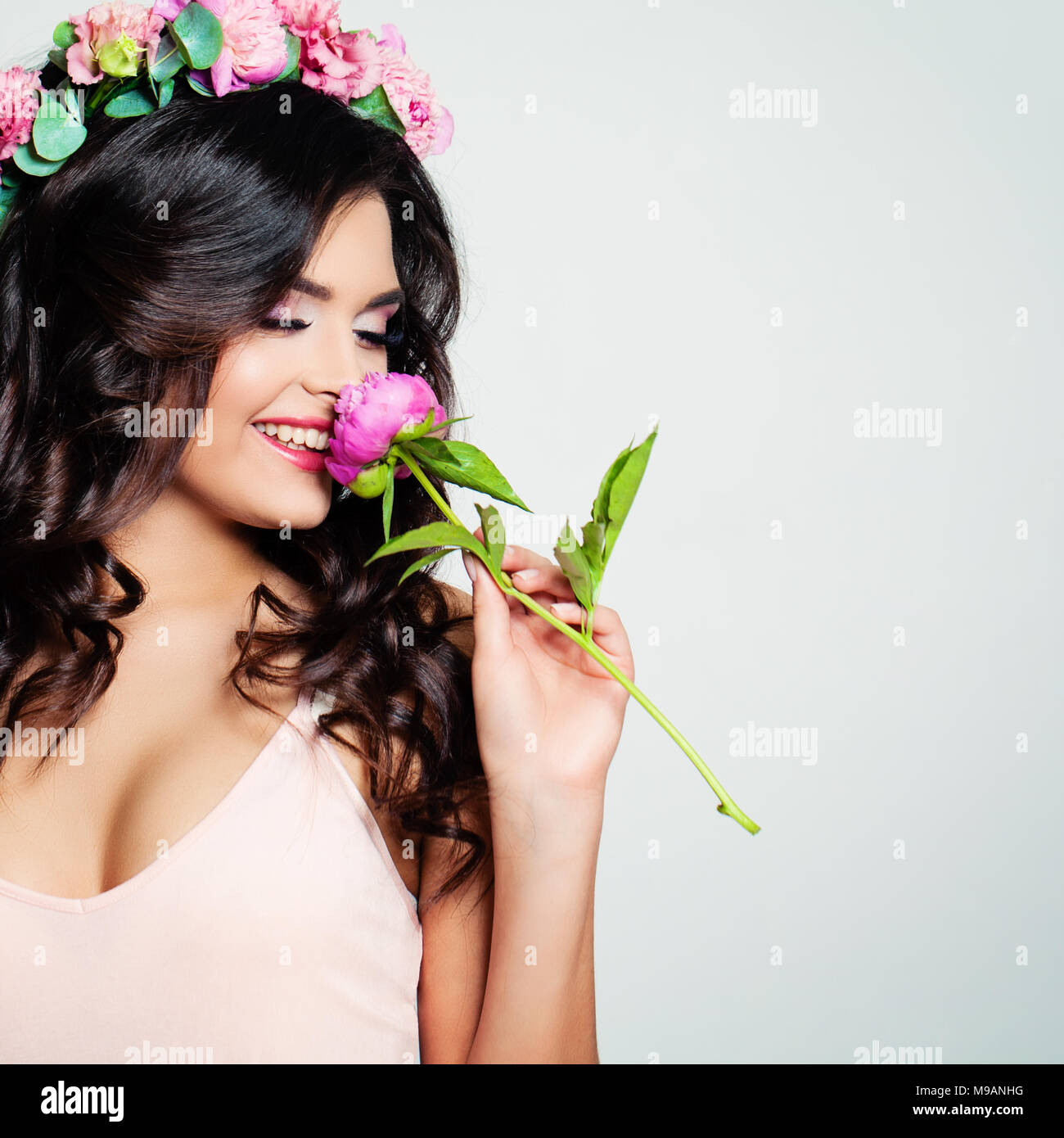 Bella Donna lo sniffing di un fiore. Bionda bellezza. Lunga permed capelli  ricci e il trucco di moda. Bellezza ragazza con fiori acconciatura. 78fd1724762d