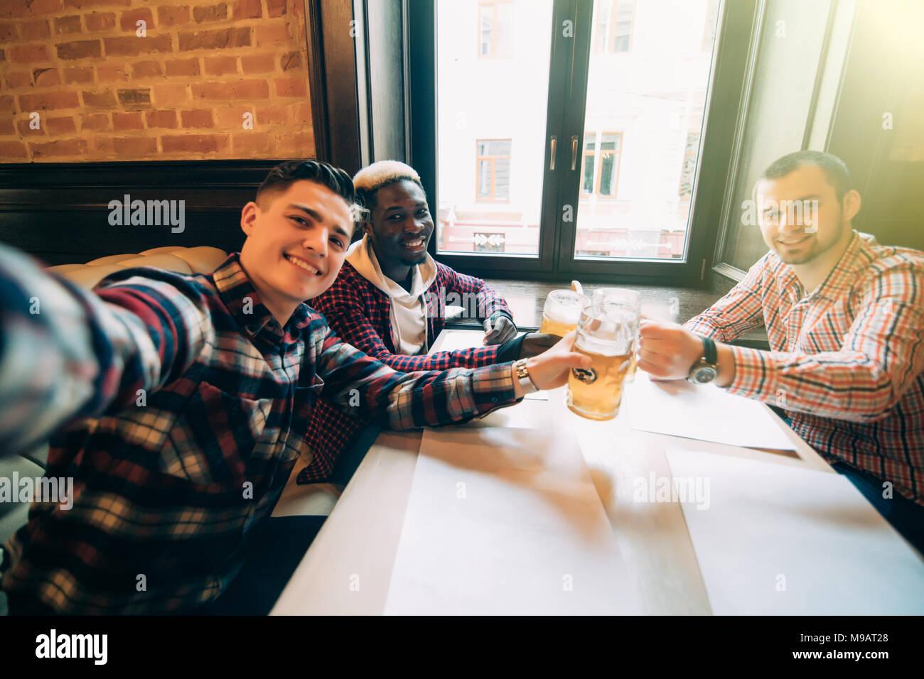 Persone, di svago, di amicizia, di tecnologia e di laurea il concetto di partito - happy amici maschi tenendo selfie e bere la birra al bar o pub Immagini Stock
