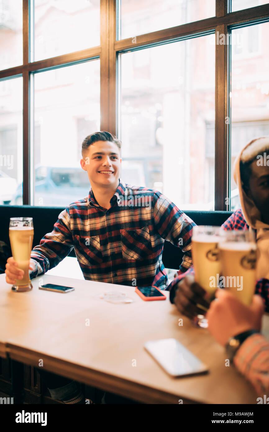 Un gruppo di uomini a bere birra e avente parlare in pub Immagini Stock