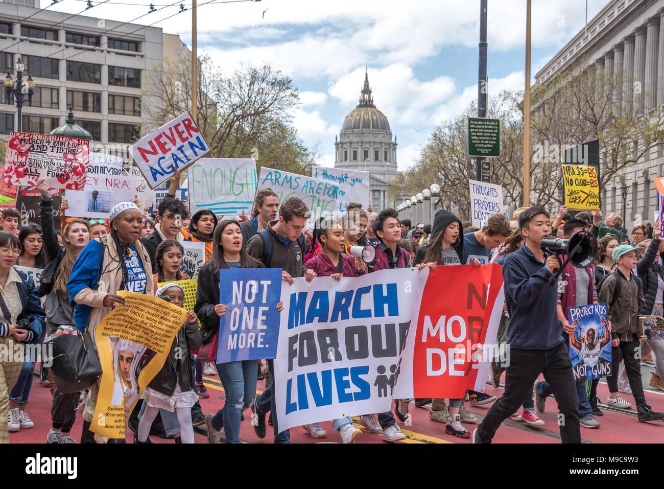 """San Francisco, Stati Uniti d'America. Il 24 marzo 2018. Marzo per la nostra vita rally e da marzo a chiamata per il controllo dell'arma e la fine della violenza pistola; la marching inizia come questi studenti portano migliaia di dimostranti dal Centro Civico lungo Market Street. Leggere i segni di 'Marco per la nostra vita,"""" """"Non uno di più"""", """"mai più"""", """"Basta' e 'Proteggi i bambini non le armi."""" Shelly Rivoli/Alamy Live News Immagini Stock"""