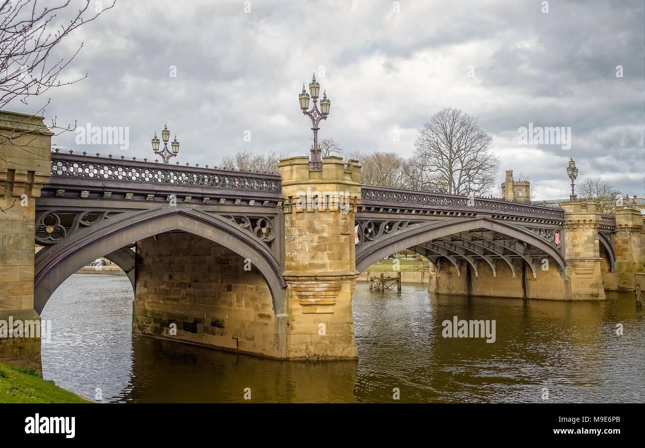 Skeldergate ornati ponte di ferro attraversa il fiume Ouse a York. Un cielo nuvoloso scuro è sovraccarico. Immagini Stock