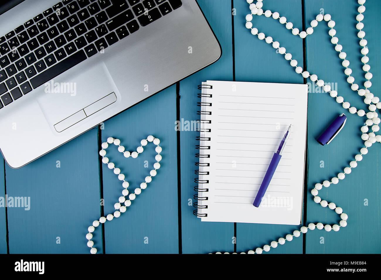 Le donne moderne workplace con notebook o computer portatile. Still Life, business, forniture per ufficio o il concetto di istruzione. Lay piatto. Vista dall'alto. Il simbolo Cuore, l'amore. Foto Stock