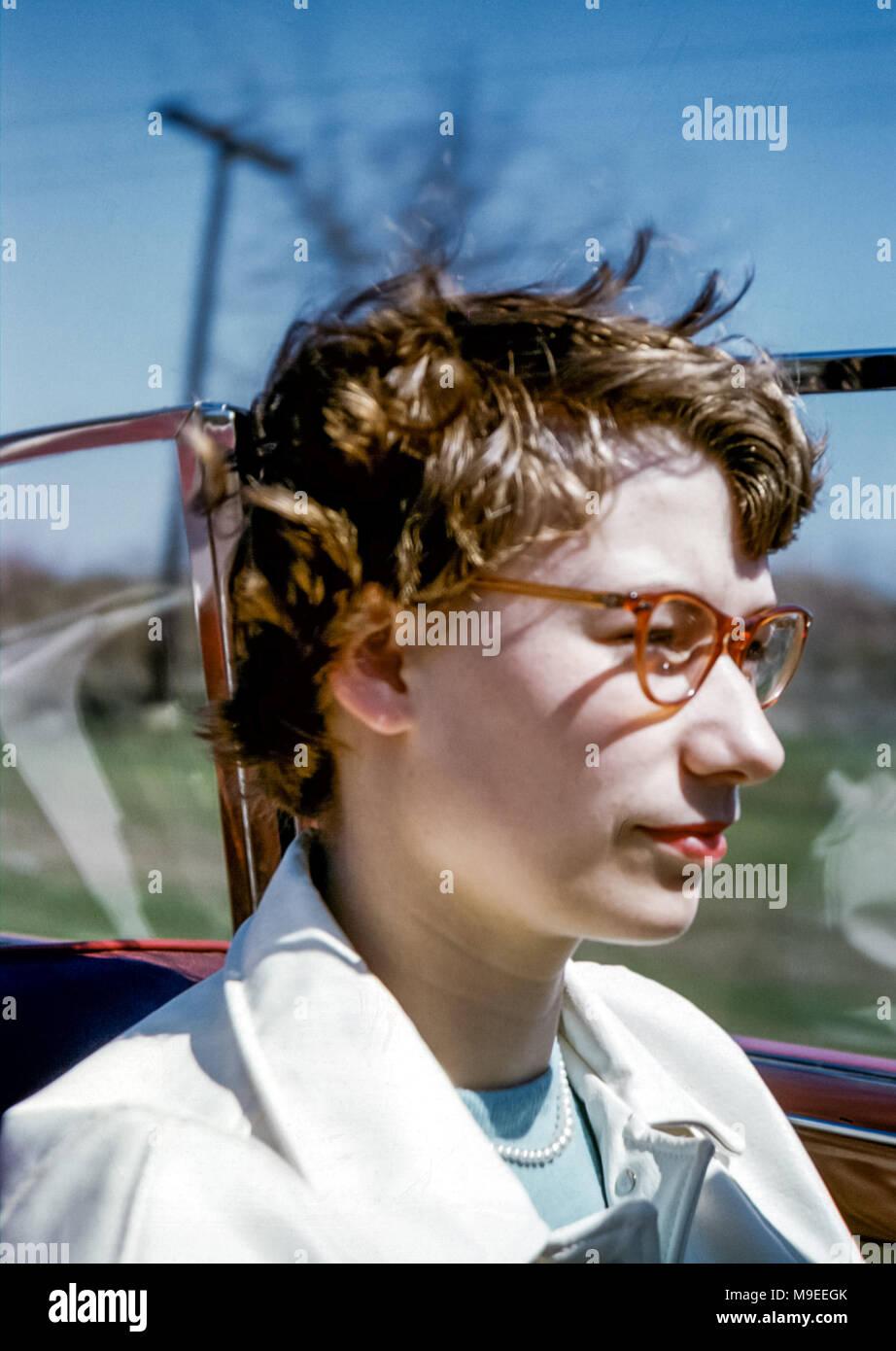 766914b79ba403 Giovane donna con gli occhiali e rossetto rosso con i capelli al vento  mentre si guida ...