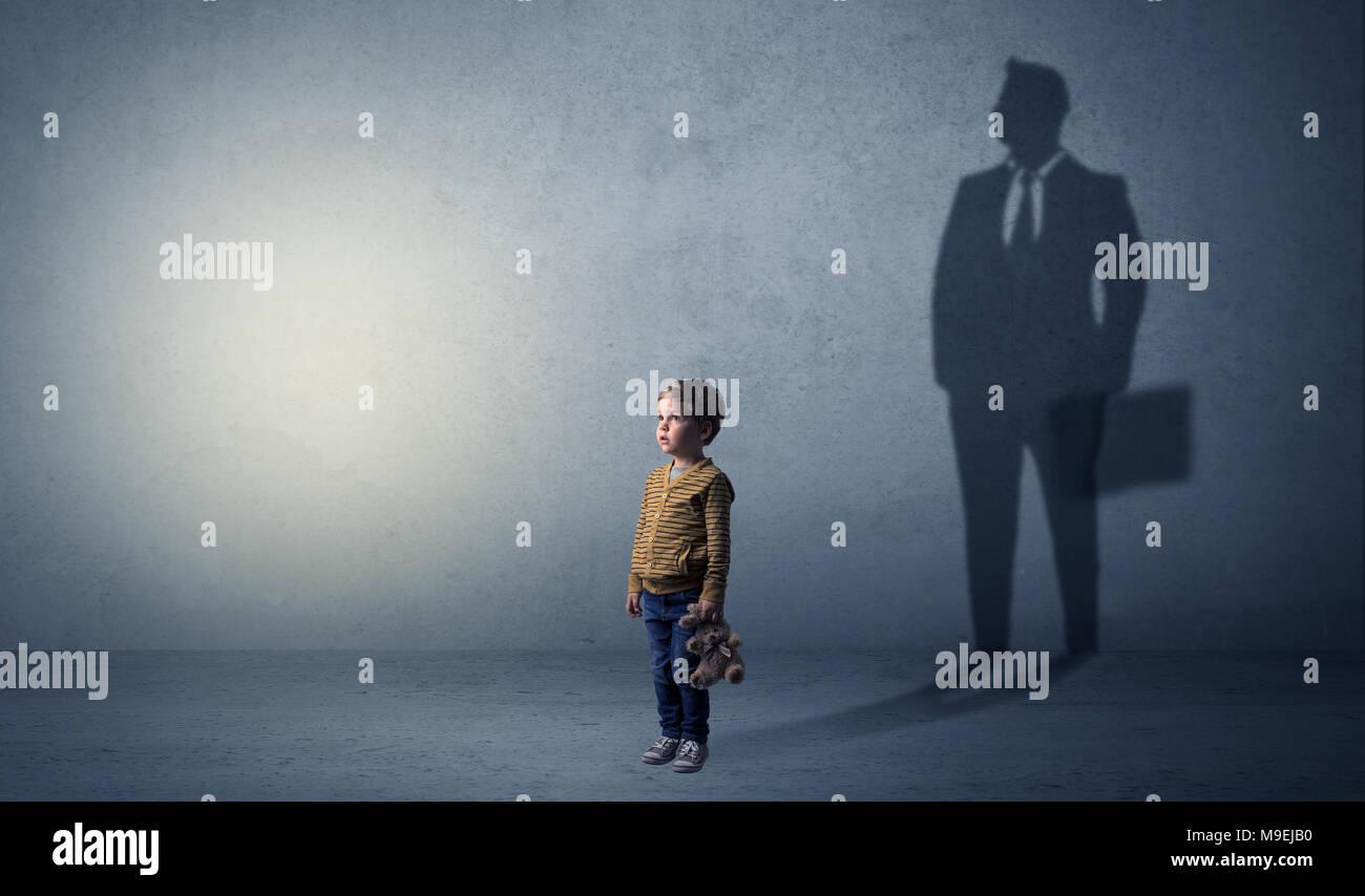 Little Boy immaginare che egli sarà uomo d affari e illustrando il suo futuro in una grande ombra Foto Stock