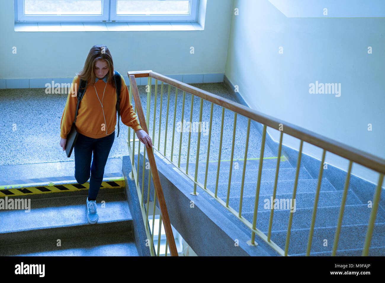 Giovani premuto lonely collegio femminile studente a piedi giù per le scale alla sua scuola, guardando verso il basso. Istruzione, bullismo, depressione concetto. Immagini Stock