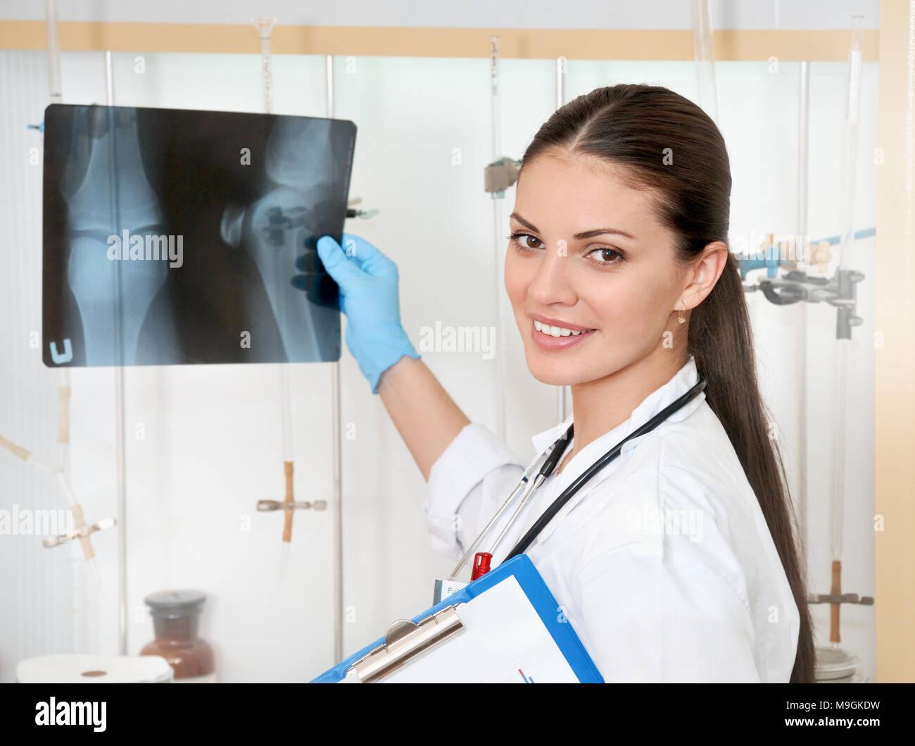 Concetto medico di giovani belle donne medico in camice bianco con roentgen in mano. La donna lavoratrice ospedale guardando roentgen e sorridente Foto Stock