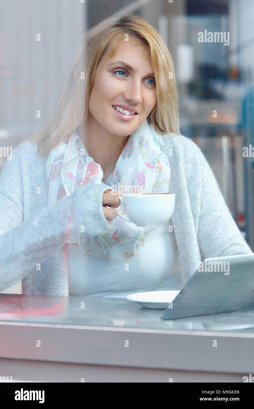 Ritratto di una ragazza pensieroso a bere caffè e guardando all'esterno attraverso una finestra. Lo stile di vita e il concetto di tecnologia Foto Stock