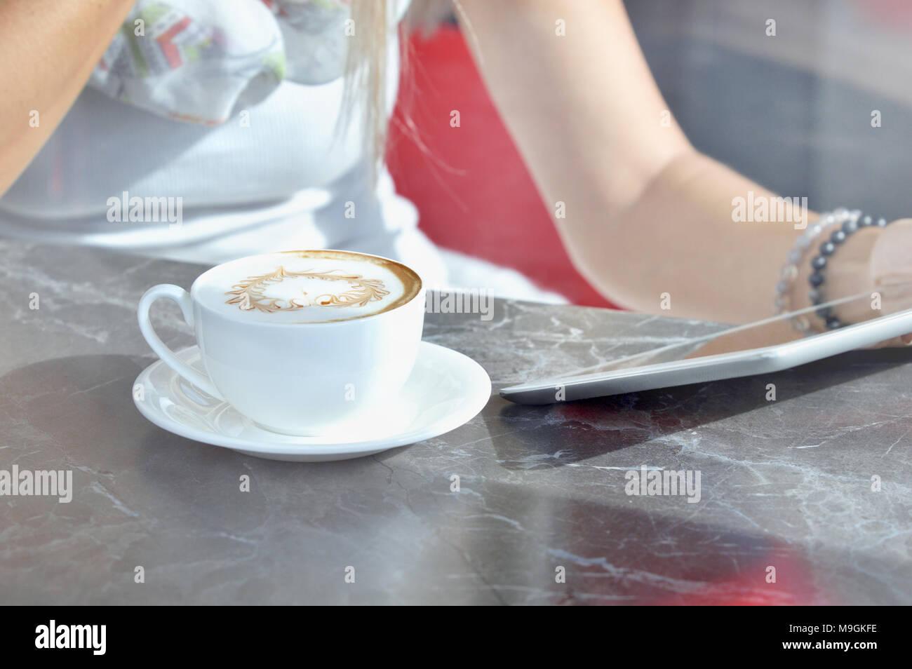 Donna usare un touch pad schermo mentre in piedi in moderno cafe'. Vi è tazza di caffè latte nelle vicinanze. Concetto di comunicazione Foto Stock