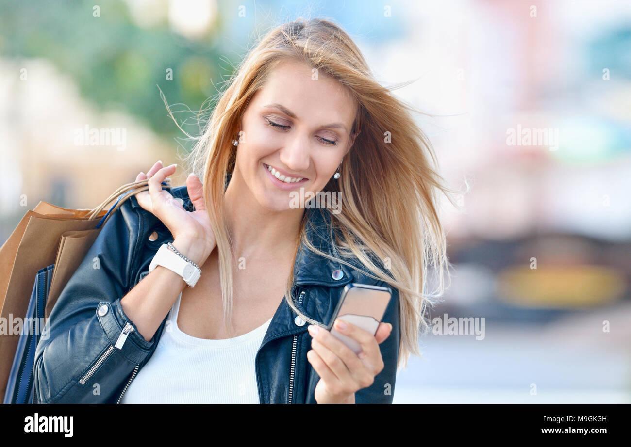 Giovane donna sorridente con sacchetti di shoping tenere premuto Telefono cellulare e guardare su di esso. Sfocate sullo sfondo di strada Foto Stock