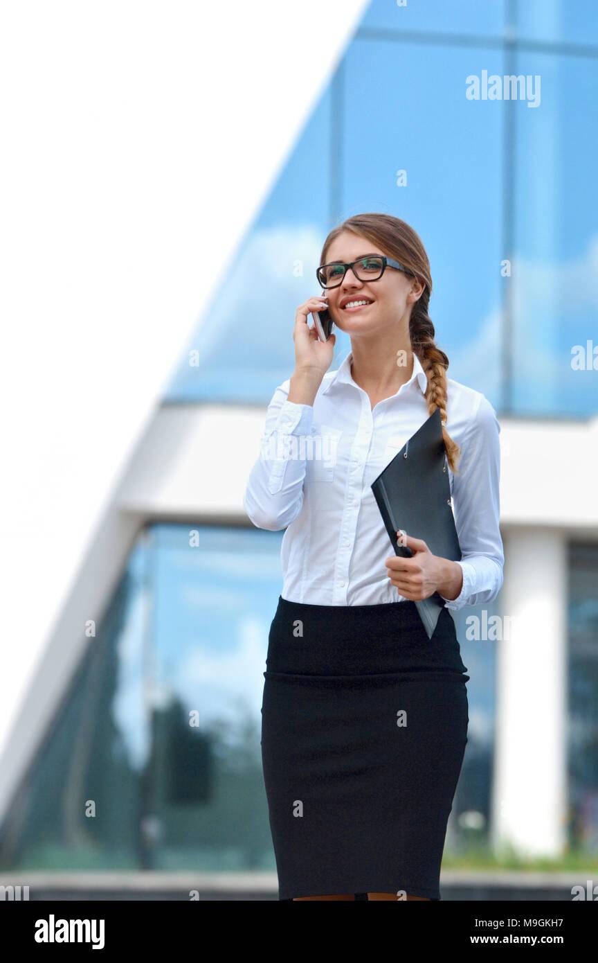 Ritratto di una imprenditrice parlando al telefono cellulare. All'aperto, sulla città. Il concetto di business Foto Stock