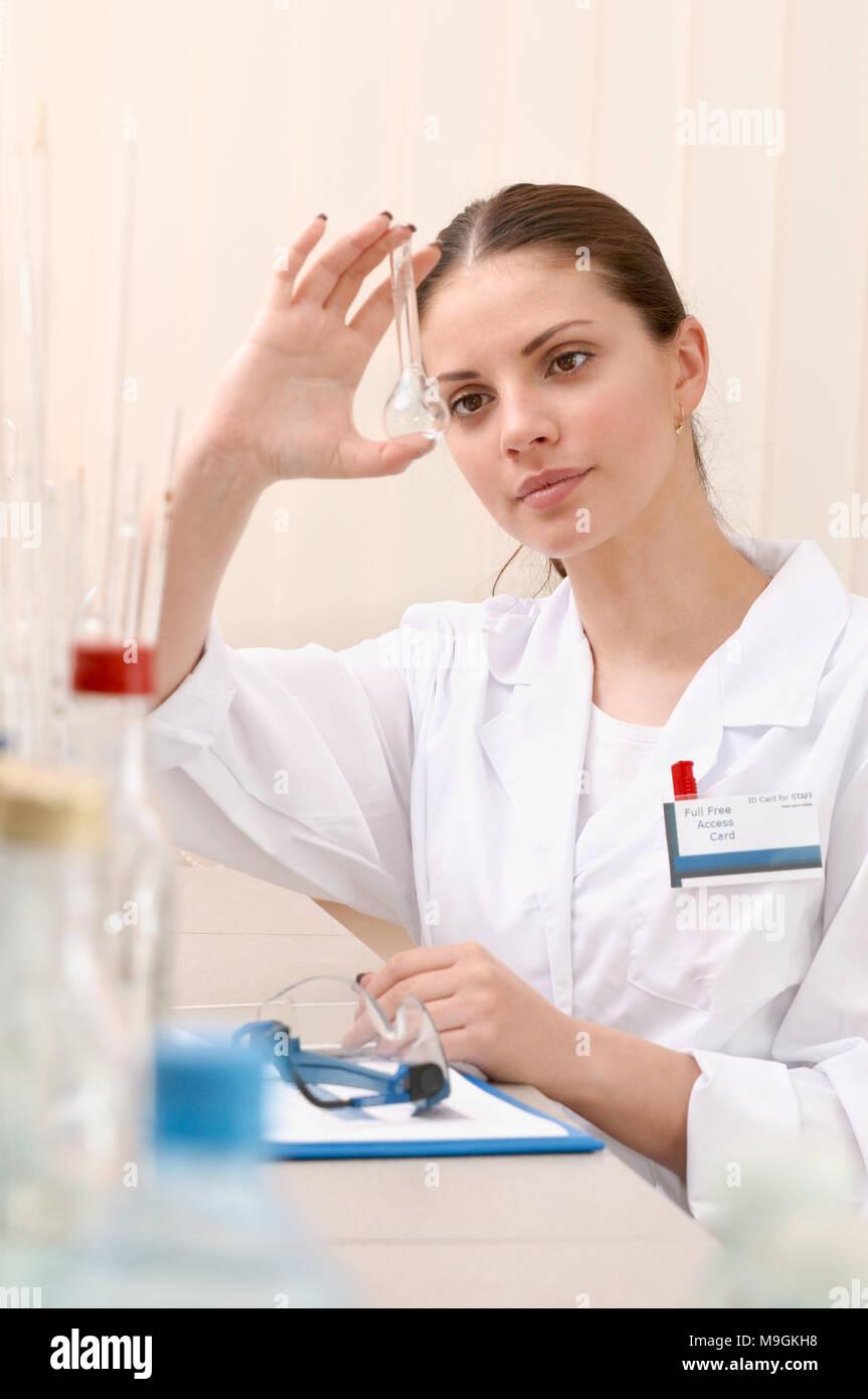 Donna assistente di laboratorio tenendo un vuoto tubo di prova e guardare da vicino su di esso. Donna scienziato ricercatore di condurre un esperimento in un laboratorio Foto Stock