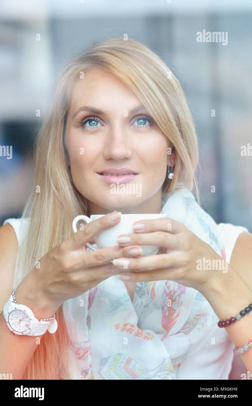 Ritratto di una ragazza pensieroso a bere caffè e guardando all'esterno attraverso una finestra. Il concetto di stile di vita Foto Stock