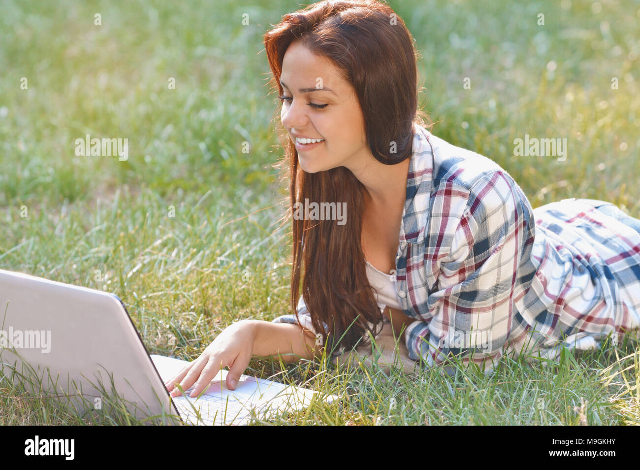 Studente ragazza che lavora su laptop giacente su erba nel parco. Studente all'esterno. Lavoro freelance, shopping online, apprendimento a distanza concetto Foto Stock