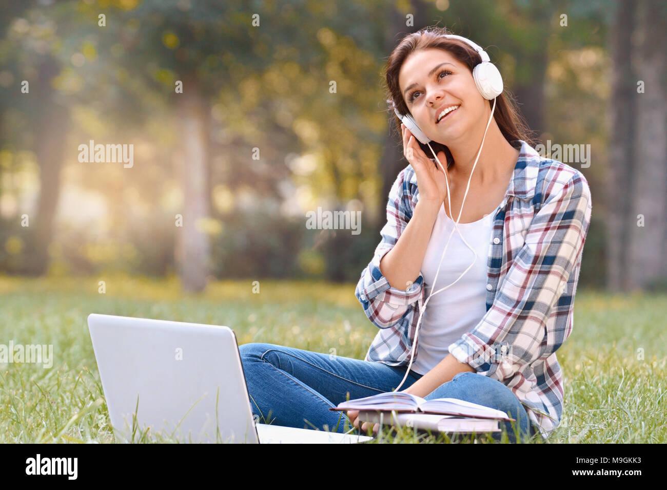 Studente ragazza che lavora sul computer portatile, seduti su erba nel parco. Studente all'esterno. Lavoro freelance, shopping online, apprendimento a distanza concetto Foto Stock