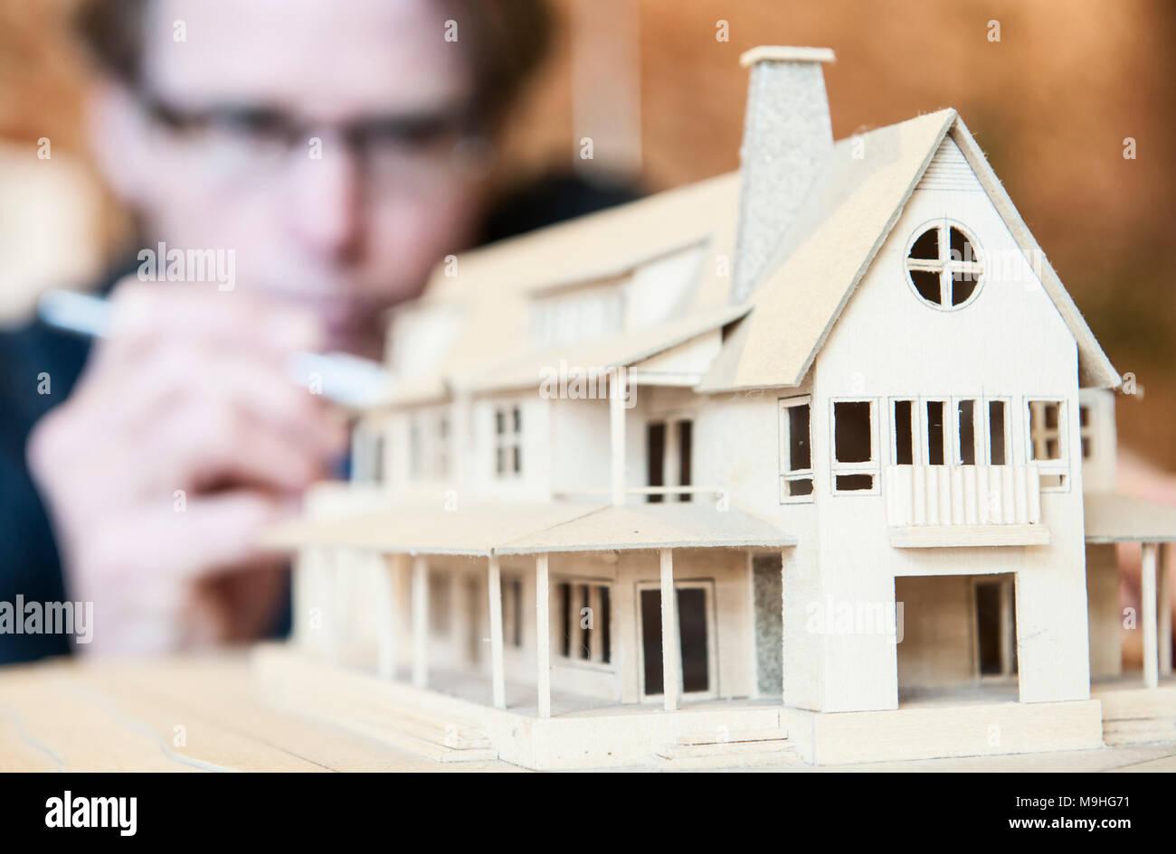 Maschio caucasico architetto operante su un modello in scala di una casa nuova. Foto Stock