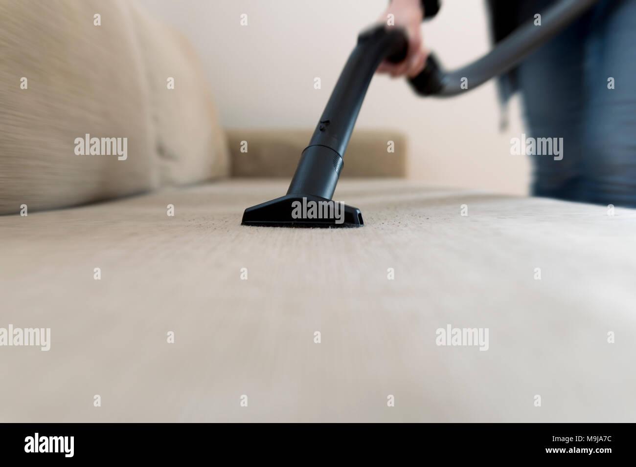 La donna la pulizia del divano, lettino con un aspirapolvere Immagini Stock