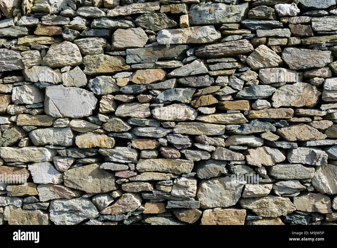 Pietre di diverse forme, dimensioni e colori in una pietra a secco muro fatto di rocce locali nel Geoparco. Rhoscolyn, Isola di Anglesey, Galles, Regno Unito, Gran Bretagna Foto Stock