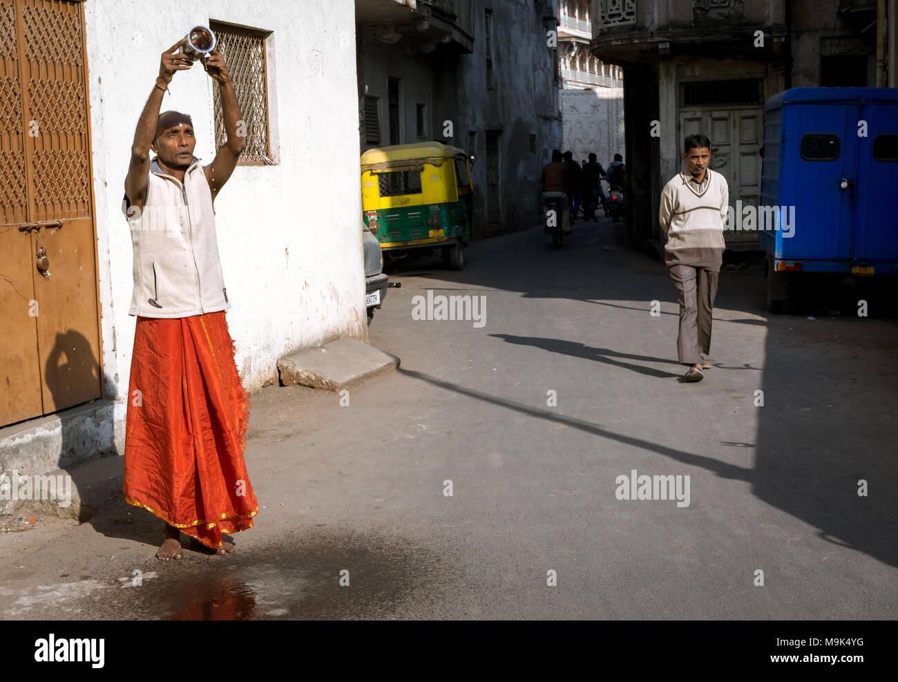 Uomo di eseguire rituali mattina offrendo acqua al sole di Dio in Ahmedabad città dell India. Recentemente riconosciuta come patrimonio mondiale città. Immagini Stock