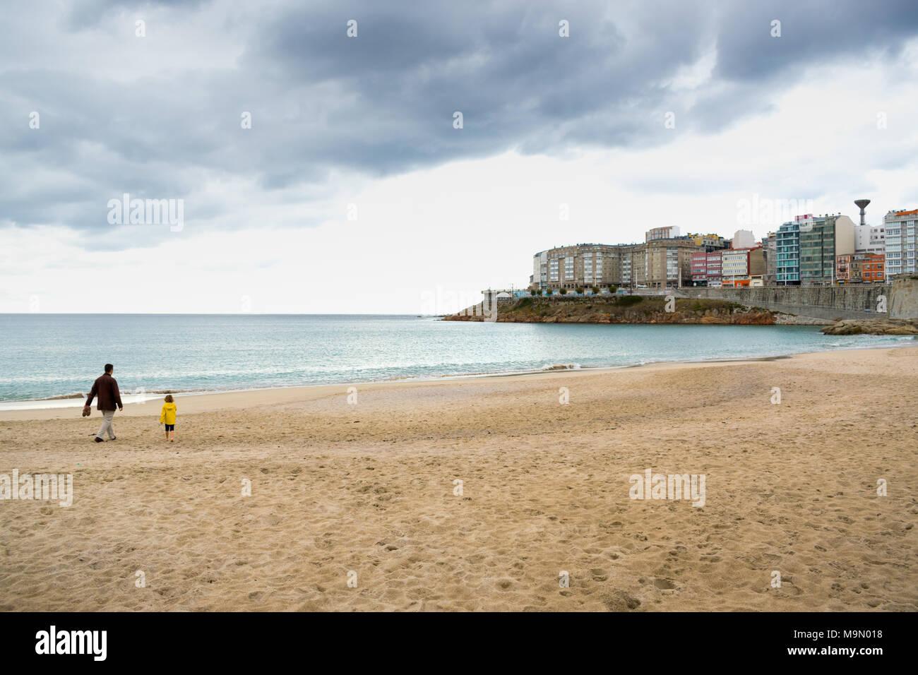 Padre e figlia a camminare su una spiaggia nel nord della Spagna sotto un cielo nuvoloso Immagini Stock