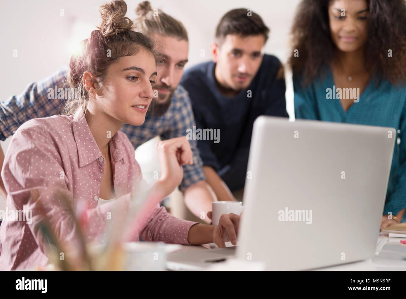 Multirazziale business team lavorano insieme attorno a un computer portatile Foto Stock