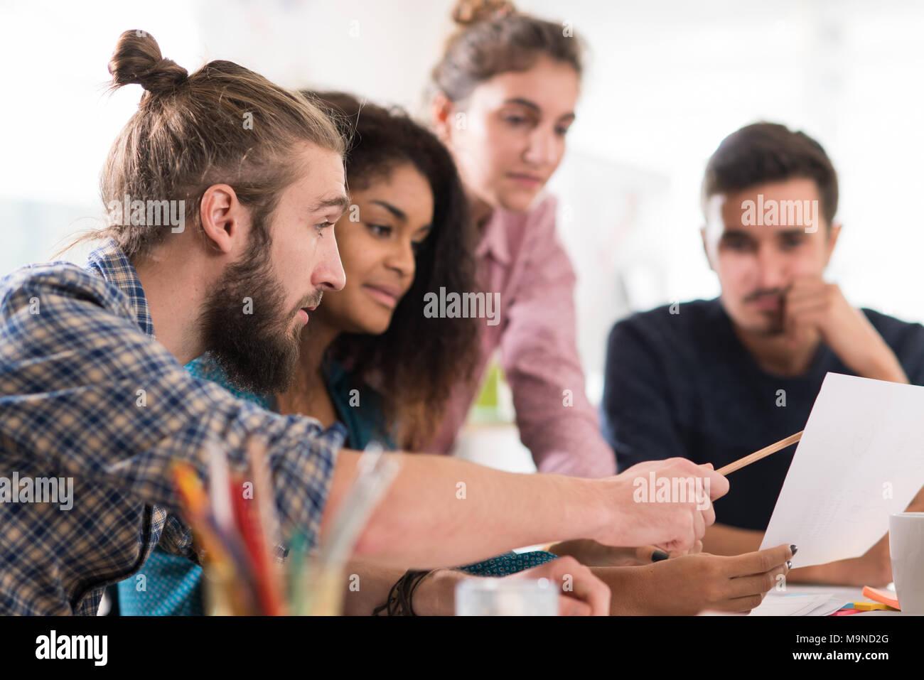 Multietnica giovane team creativo di condividere idee su un progetto Immagini Stock