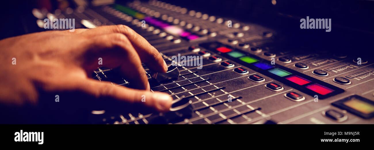 Ritagliate la mano del musicista con mixer audio Immagini Stock