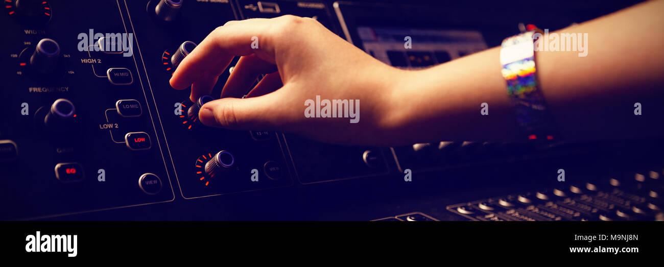Ritagliate la mano del tecnico audio con mixer audio Immagini Stock