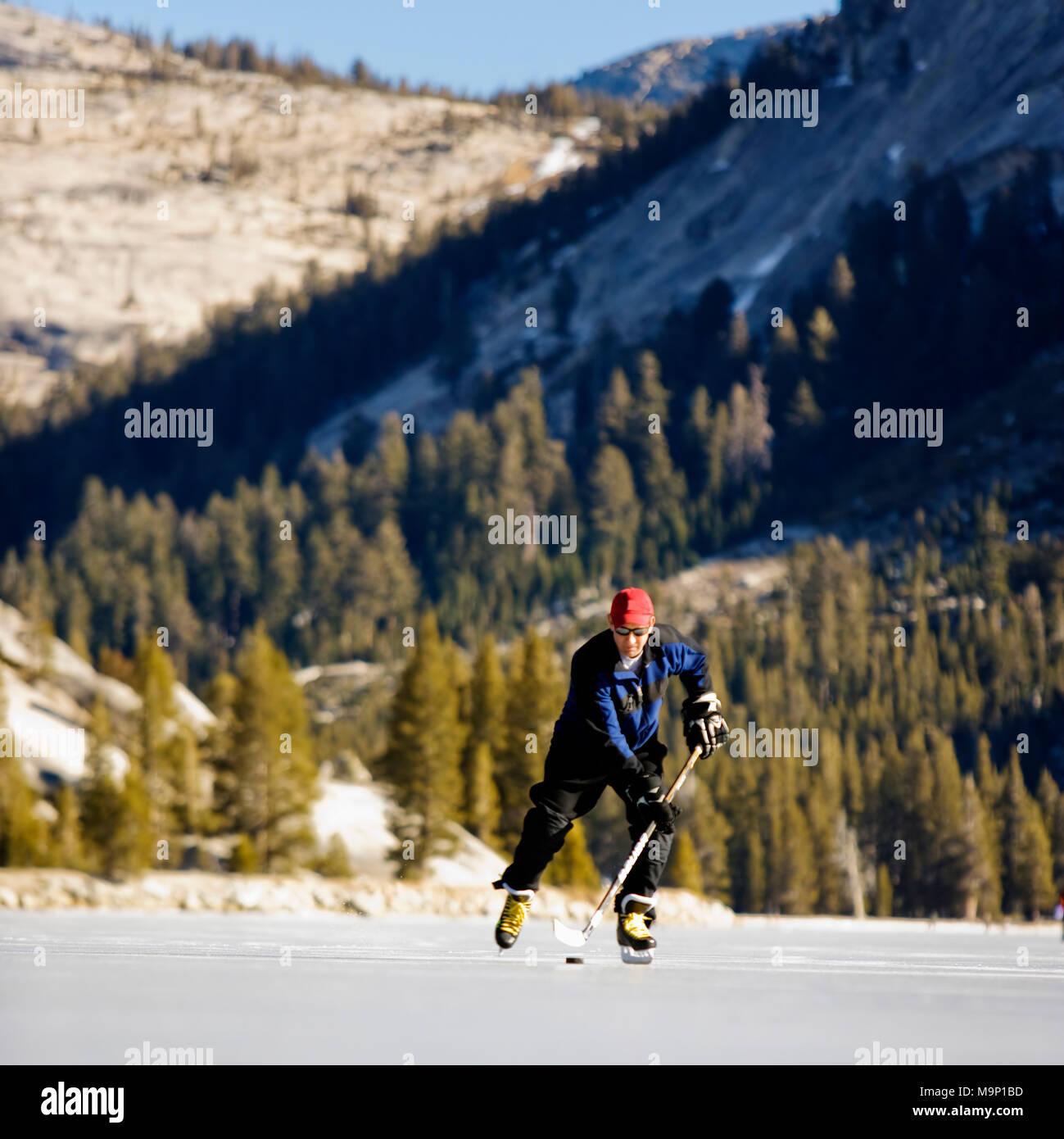 Basso angolo vista frontale di un pattinatore su ghiaccio la riproduzione di hockey su ghiaccio su una neve libera, congelati Tenaya Lake nel Parco Nazionale di Yosemite. Immagini Stock