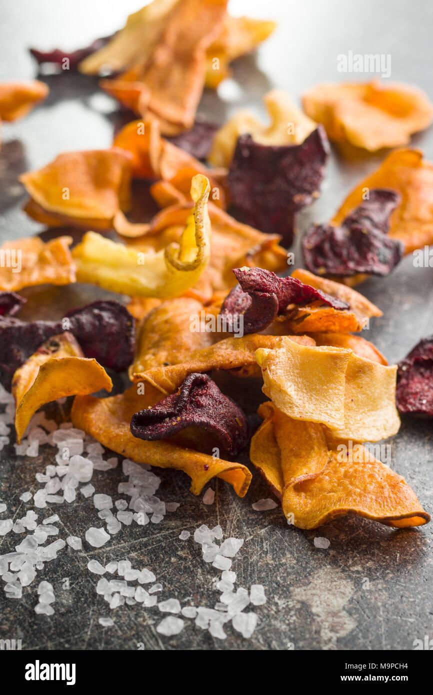 Fritto misto di chip di vegetali e sale sulla vecchia tabella. Immagini Stock