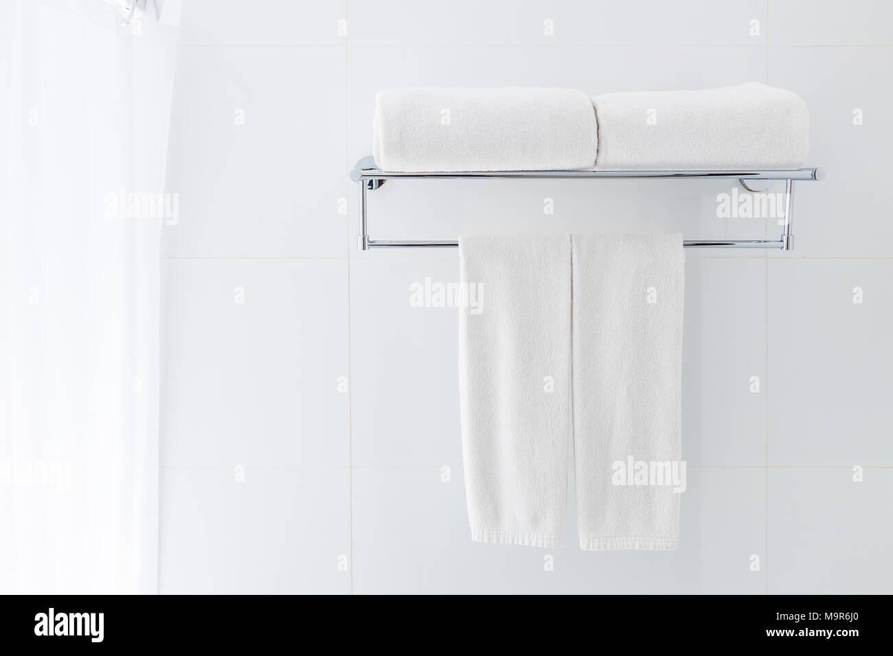 Bianco asciugamani da bagno appeso sul rack in un bagno bianco