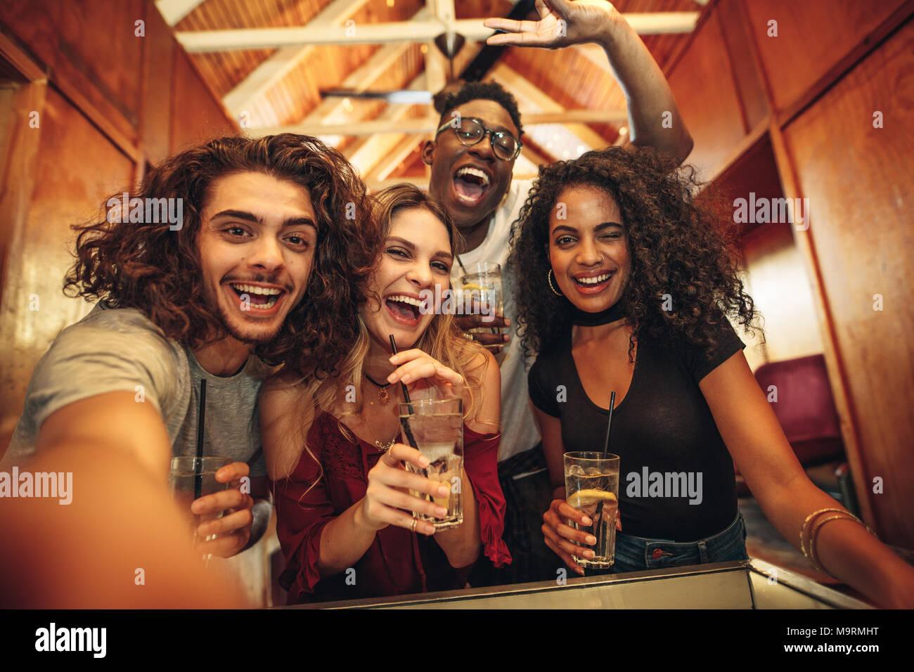 Gruppo di felice giovani amici con bevande raccolte per party in club. Entusiasti di uomini e una donna con drink prendendo selfie durante il party. Immagini Stock