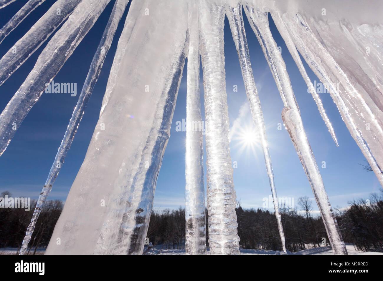 Grandi ghiaccioli appesi al sole di mezzogiorno. Foto Stock