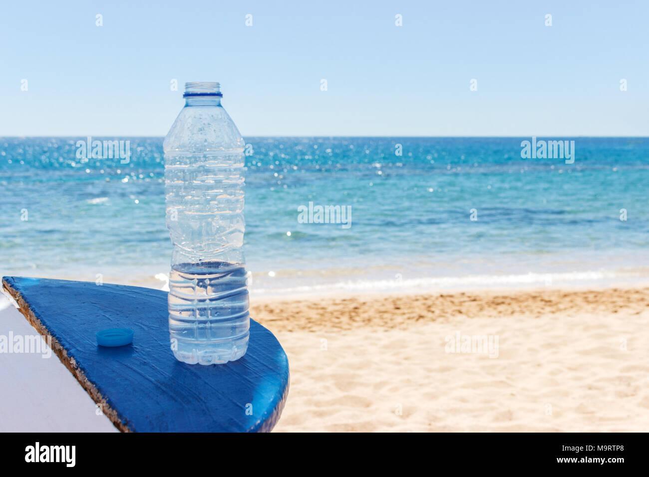 Bottiglia di acqua sulla spiaggia la tabella sotto il cielo aperto