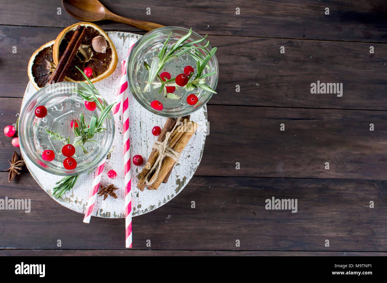 Un cocktail rinfrescante con mirtillo rosso, il rosmarino e il ghiaccio, due, Vetro scuro dello sfondo , la bevanda alcolica, spazio di copia Immagini Stock