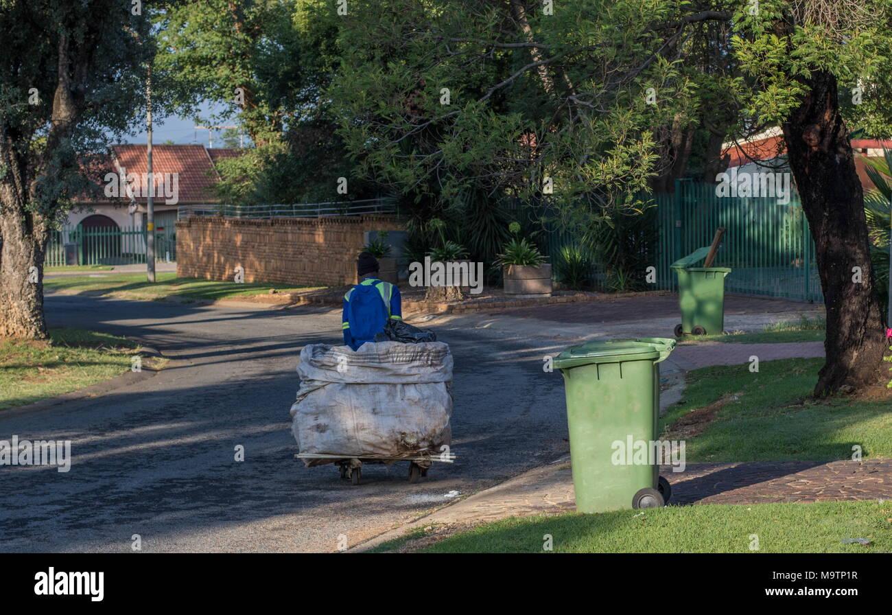 Johannesburg, Sud Africa - disoccupati non identificato uomo utilizza un carrello realizzato localmente per raccogliere prodotti riciclabili per la rivendita da famiglia cassonetti Immagini Stock