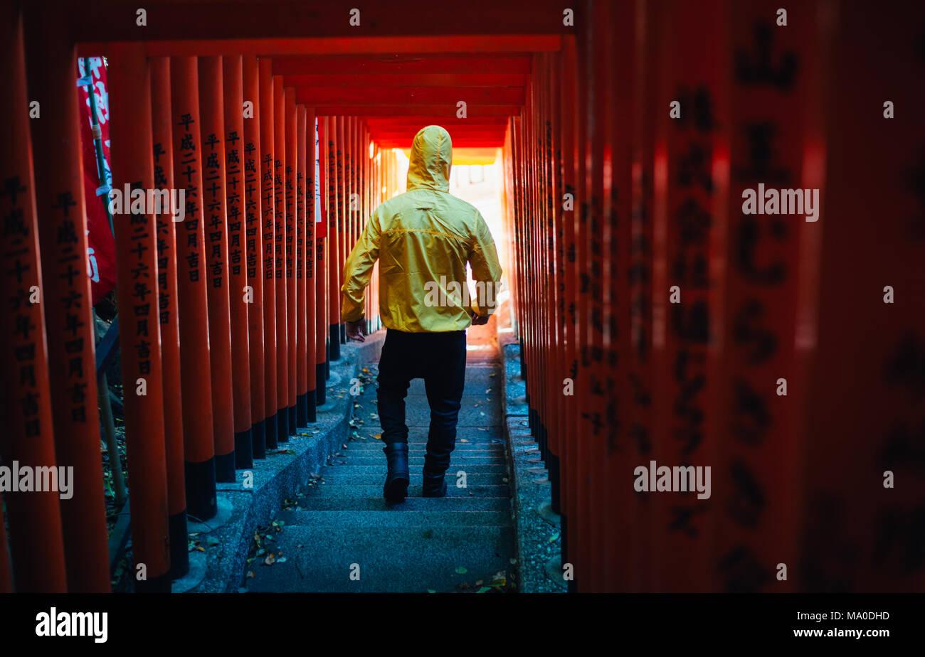 Uomo a camminare sotto un giapponese di tori santuario Immagini Stock