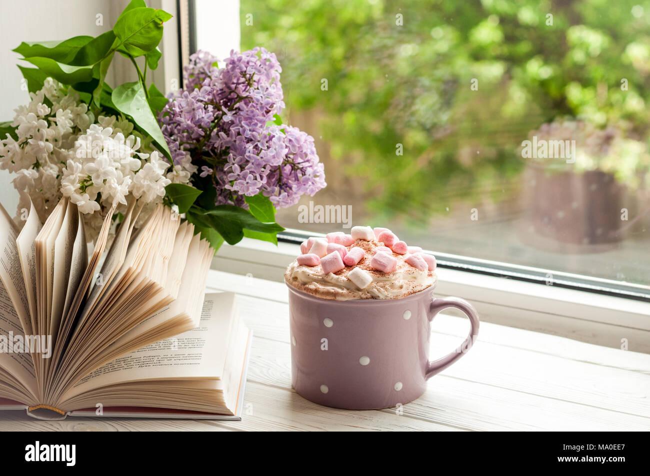 tazza da caff con marshmallow libro aperto e bouquet di