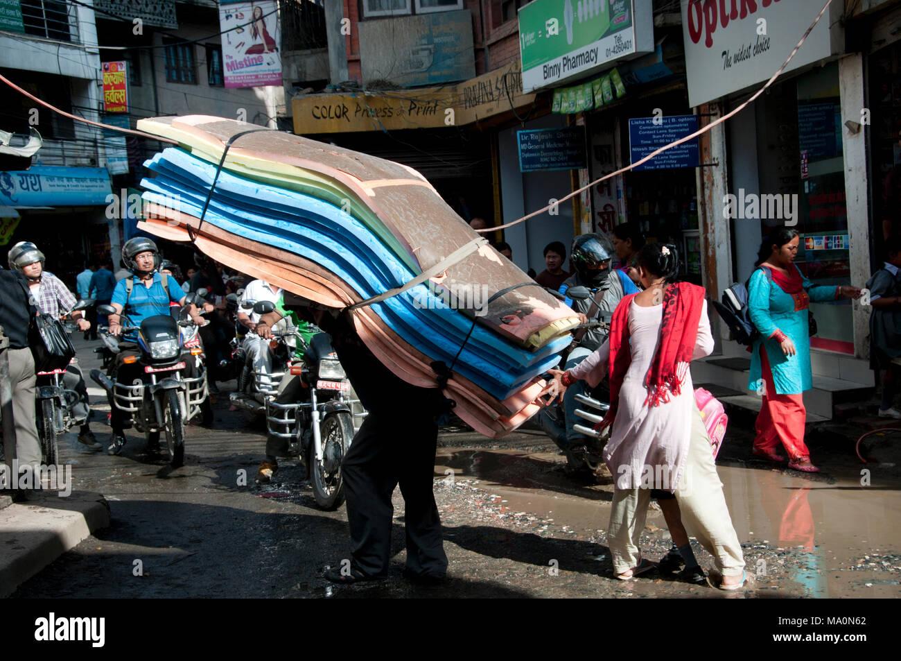 Il Nepal 2014. Kathmandu . L'uomo portando materassi accanto agli uomini sulla moto. Foto Stock